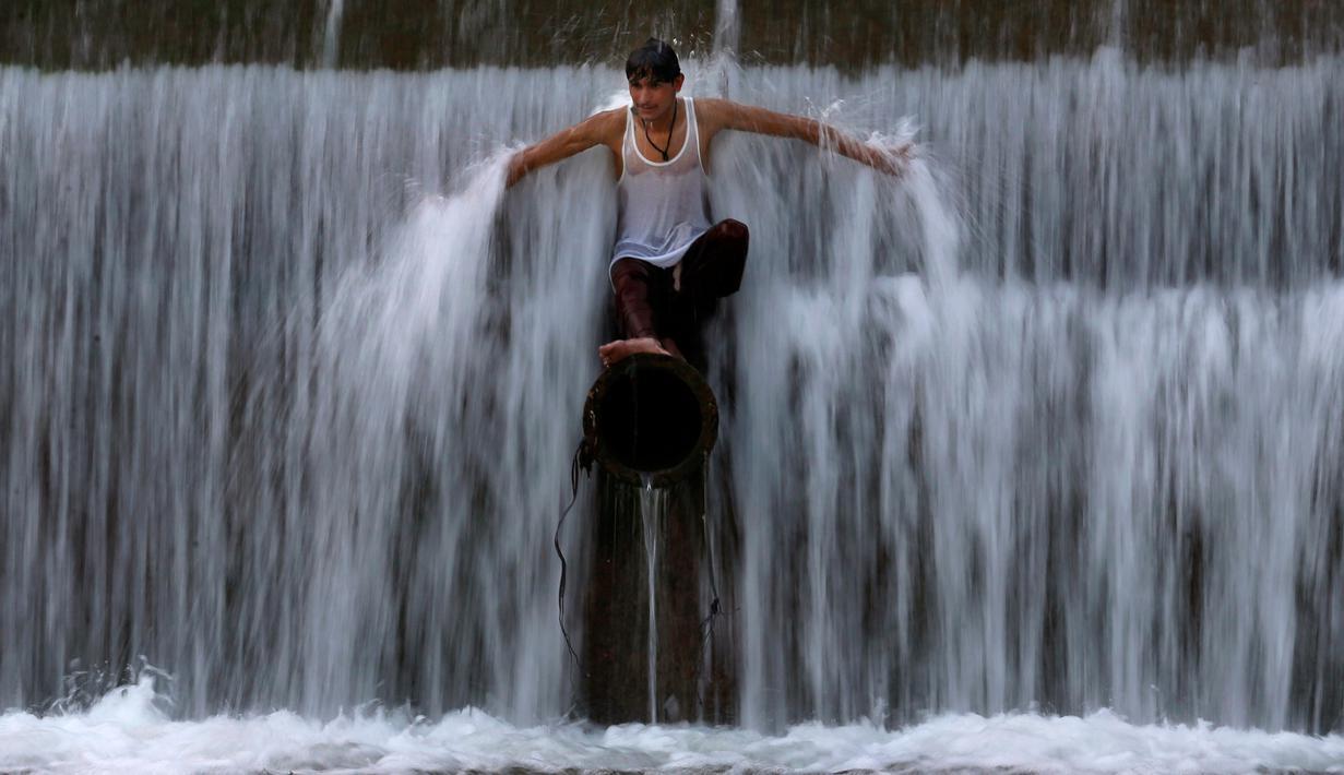 Seorang pria Pakistan mendinginkan diri dalam arus air ketika suhu mencapai 40 derajat celsius di Islamabad pada Rabu (27/5/2020). Banyak kota di Pakistan menghadapi kondisi gelombang panas dengan suhu mencapai 50 derajat celsius di beberapa tempat.  (AP Photo/Anjum Naveed)