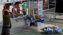 Peserta berusaha mengendalikan robot untuk mendaki sebuah kastil dalam kompetisi robot San Diego Regional FIRST Robotics di Del Mar, California (4/3). Kompetisi tahunan San Diego ke-10 ini diikuti oleh puluhan tim dari SMA di AS. (REUTERS / Mike Blake)