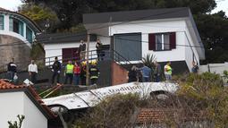 Orang-orang melihat kondisi sebuah bus pariwisata berisi rombongan turis dari Jerman yang terguling di Kota Canico, Pulau Madeira, Portugal, Rabu (17/4). Warga setempat melaporkan bahwa cuaca baik-baik saja pada saat kecelakaan, yang terjadi di sore hari. (RUI SILVA / AFP)