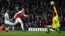 Kiper Bournemouth Artur Boruc gagal menghalau bola dari pemain Arsenal, Mesut Ozil yang menjebol gawangnya pada laga lanjutan Liga Inggris, 2018-19 pekan ke-28 di Emirates Stadium, Rabu (27/2). Arsenal menang dengan skor telak 5-1. (Ian KINGTON/AFP)