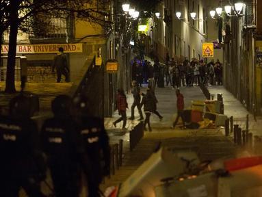 Petugas polisi saat terlibat bentrok dengan imigran di Madrid, Spanyol, Kamis (15/3). Bentrokan berawal dari aksi protes imigran atas meninggalnya seorang pedagang jalanan asal Senegal. (AFP Photo/Olmo Calvo)
