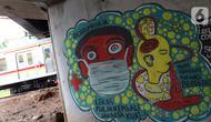 KRL melintas di dekat mural bertema pencegahaan penyebaran virus Corona atau COVID-19 di Jakarta, Selasa (7/4/2020). Mural tersebut menghimbau masyarakat untuk menjaga jarak fisik dan selalu menggunakan masker serta tetap beraktivitas di dalam rumah. (Liputan6.com/Helmi Fithriansyah)