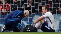 Penyerang Tottenham Hotspur, Harry Kane (kanan) mendapat perawatan tim medis setelah mengalami cedera saat melawan Bournemouth di Liga Inggris di Stadion Vitalitas di Bournemouth (11/3). Kane mengalami cedera pergelangan kaki. (AFP Photo/Adrian Dennis)