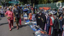 Warga melintasi pedagang kaki lima (PKL) yang berjualan di kawasan Jalan Sumenep, Jakarta, Minggu (17/11/2019). Jalan Sumenep dan Jalan Pamekasan merupakan titik yang sudah ditentukan untuk berjualan saat car free day (CFD). (Liputan6.com/Faizal Fanani)