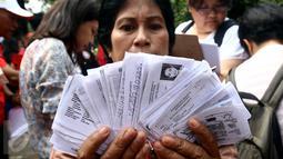 Warga menunjukan KTP yang telah terkumpul saat pengumpulan KTP di depan Balai Kota, Jakarta, Kamis (5/11). Pendataan dan pengumpulan KTP tersebut sebagai petisi penangguhan penahanan Ahok sebagai Tahanan Kota. (Liputan6.com/Johan Tallo)