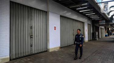 Petugas keamanan berjalan di depan pertokoan kawasan perdagangan Pasar Baru yang tutup, Jakarta, Jumat (3/4/2020). Sebagian pemilik toko di Pasar Baru memilih menutup usahanya sementara waktu untuk mengantisipasi meluasnya penyebaran virus corona COVID-19. (Liputan6.com/Faizal Fanani)