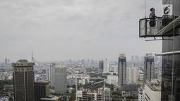 Pekerja tanpa helm keselamatan beraktivitas di gedung bertingkat di Jakarta, Rabu (15/11). Banyak kejadian kecelakaan kerja di ketinggian disebabkan karena minimnya pengetahuan dasar mengenai keselamatan kerja di ketinggian. (Liputan6.com/Faizal Fanani)