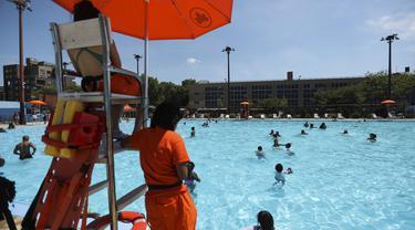 Sejumlah petugas penyelamat terlihat bertugas di samping sebuah kolam renang di New York, Amerika Serikat (27/7/2020). Gelombang panas melanda New York City pada Senin (27/7) dengan suhu tertinggi mencapai lebih dari 36 derajat Celsius. (Xinhua/Wang Ying)