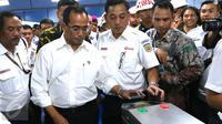 Menhub Budi Karya Sumadi menempelkan e-tiket pada reader gate sebelum naik KRL di Stasiun Juanda, Jakarta, Rabu (10/8). Menhub Budi meninjau proyek pembangunan kereta bandara Soekarno Hatta yang akan terintegrasi dari Jakarta. (Liputan6.com/Angga Yuniar)