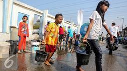Sejumlah anak membawa ember yang berisi air bersih di kawasan Muara Angke, Jakarta, Selasa (4/8/2015). Memasuki musim kemarau, warga kesulitan mendapatkan air bersih karena beberapa sumber air mengalami kekeringan. (Liputan6.com/Faizal Fanani)