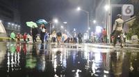 Masyarakat mulai memadati car free night di kawasan Thamrin, Jakarta, Selasa (31/12/2019). Meski diguyur hujan masyarakat mulai memadati kawasan tersebut untuk menikmati malam pergantian tahun 2019. (Liputan6.com/Angga Yuniar)