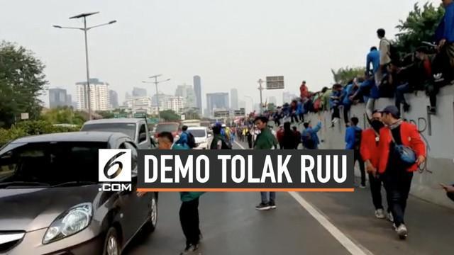 Mahasiswa yang menggelar demonstrasi di depan Gedung DPR RI menutup jalan tol dalam kota yang membentang di depan Gedung DPR.