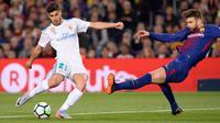 Gelandang Real Madrid, Marco Asensio berebut bola dengan bek Barcelona, Gerard Pique pada pertandingan La Liga Spanyol di Stadion Camp Nou, Minggu (6/5). Barcelona bisa memaksakan hasil imbang dengan Real Madrid 2-2. (AFP/Josep LAGO)