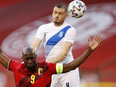 Striker Belgia, Romelu Lukaku, duel udara dengan pemain Yunani, Kyriakos Papadopoulos, pada laga uji coba di Stadion King Baudouin, Jumat (4/6/2021). Kedua tim bermain imbang 1-1. (AP/Francisco Seco)