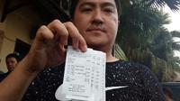 Riski Riswandi, pemilik warung nasi bebek menunjukkan nota transaksi pembelian palsu yang diambil paksa dari tangan pengemudi transportasi online di Kota Malang (Liputan6.com/Zainul Arifin)