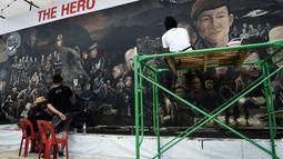 Seniman lokal menyelesaikan mural berjudul 'The Heroes' di Chiang Rai, 18 Juli 2018. Tampak lukisan wajah Saman Gunan, mantan penyelam AL Thailand yang meninggal dunia saat membantu operasi penyelamatan tim sepak bola Wild Boars. (AFP/Lillian SUWANRUMPHA)