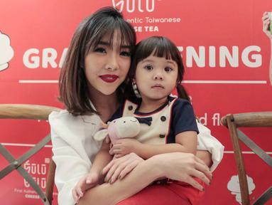 Selebritas Gisella Anastasia berpose bersama sang anak Gempita Nora Marten saat menghadiri pembukaan stan produk minuman di Jakarta, Jumat (23/3). Gisel mengaku bahwa Gempi menyaingi ketenarannya sebagai pesohor hiburan. (Liputan6.com/Faizal Fanani)