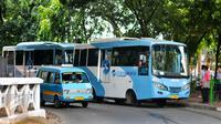 Bus pengumpan atau feeder bus Transjakarta sedang ngetem menunggu penumpang di seberang Stasiun Tebet , Jakarta, Kamis (7/4). Pengoperasian ini bagian dari antisipasi penumpukan penumpang saat perlintasan KRL Tebet ditutup. (Liputan6.com/Yoppy Renato)