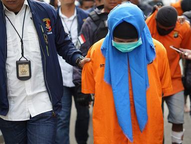 Tersangka kasus istri bunuh dan bakar suami serta anak tiri tertunduk saat dihadirkan di Polda Metro Jaya, Jakarta, Senin (2/9/2019). Polisi membekuk empat tersangka terkait pembunuhan ECP dan MAP. (Liputan6.com/Immanuel Antonius)