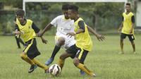 Pemain SSB Galunggung FC berusaha melewati kepungan pemain SSB Tulehu Putra pada semifinal turnamen Liga Remaja UC News di Lapangan Masariku Yonif 733, Ambon, Rabu (29/11/2017). (Bola.com/Peksi Cahyo)