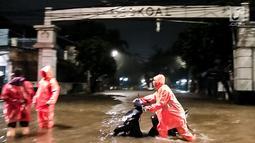 Pengendara mendorong motor saat banjir menggenangi kawasan Simpang Seskoal, Kebayoran Lama, Jakarta, Sabtu malam (16/2). Akibat banjir tersebut pengguna jalan diarahkan ke Jalan Panjang Cidodol atau putar balik ke Kebayoran Lama. (Liputan6.com/Septian)