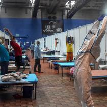 Seorang dokter yang mengenakan setelan Alat Pelindung Diri memberikan instruksi kepada pasien saat melakukan yoga di dalam bangsal di kompleks olahraga Commonwealth Games (CWG) Village yang sementara diubah menjadi pusat perawatan Covid-19 di New Delhi, India, Kamis (16/7/2020). (Money SHARMA / AFP)
