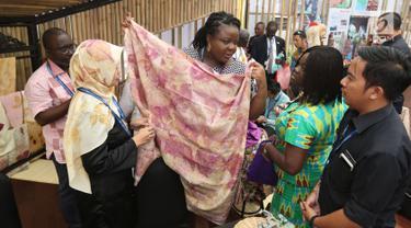 Delegasi Pertemuan Tahunan IMF-Bank Dunia melihat-lihat kain saat mengunjungi pameran Indonesia Pavilion di Nusa Dua, Bali, Minggu (14/10). Lebih dari 20 ribu delegasi mengunjungi Indonesia Pavilion selama 7 hari. (Liputan6.com/Angga Yuniar)