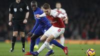 Gelandang Arsenal, Aaron Ramsey, berebut bola dengan gelandang Chelsea, N'Golo Kante, pada laga Premier League di Stadion Emirates, Sabtu (19/1). Arsenal menang 2-0 atas Chelsea. (AP/Frank Augstein)