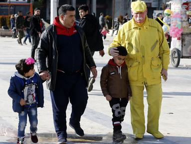 Abu Zakkour yang dijuluki 'Yellow Man' berjalan bersama pejalan kaki di alun-alun pusat Saadallah al-Jabiri, kota Suriah utara pada 11 Februari 2019. Kakek berusia 70 tahun tersebut yang hanya mengenakan pakaian kuning selama hampor 36 tahun, sejak 25 Januari 1983. (LOUAI BESHARA / AFP)