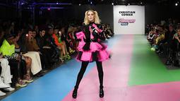 Paris Hilton membawa anjing saat tampil dalam Christian Cowan x The Powerpuff Girls Fashion Show, Los Angeles, AS, Jumat (8/3). Paris Hilton memamerkan gaun tulle merah muda bercampur hitam cerah. (Charley Gallay/Getty Images North America/AFP)