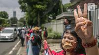 Seorang pengunjuk rasa mengangkat tiga jari saat aksi solidaritas di depan Kedubes Myanmar, Jakarta, Rabu (10/3/2021). Dalam aksi solidaritas tersebut massa mengutuk keras atas kudeta militer dan mendesak penegakan demokrasi serta perlindungan HAM di Myanmar. (Liputan6.com/Faizal Fanani)