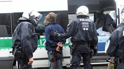 Polisi membawa aktivis lingkungan dari sebuah rumah pohon di hutan Hambacher Forst di Kerpen, Jerman Barat (13/9). Aktivis yang tinggal di rumah pohon tersebut menghadapi penggusuran paksa oleh polisi. (Henning Kaiser/dpa/AFP)