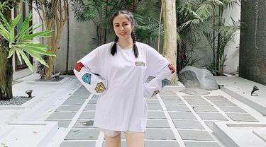 Tampil casual dengan kaus lengan panjang berwarna putih, Momo Geisha memilih untuk membuat dua kepang pada rambutnya. Gaya santai ibu dua anak ini pun berhasil curi perhatian netizen. (Liputan6.com/IG/@therealmomogeisha)