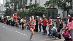 Warga menyaksikan lomba lari maraton putri Asian Games 2018 di kawasan MH Thamrin, Jakarta, Minggu (26/8). Meski Car Free Day ditiadakan, warga Ibu Kota tetap memadati kawasan MH Thamrin menyaksikan maraton Asian Games 2018. (Merdeka.com/Iqbal S. Nugroho)