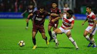 Perebutan bola antara pemain PSM Makassar dan Madura United dalam leg pertama semifinal Piala Indonesia 2018 di Stadion Andi Mattalatta Mattoangin, Makassar, Minggu (30/6/2019). PSM menang tipis 1-0 dalam pertandingan ini. (Bola.com/Abdi Satria)