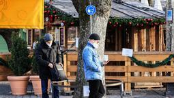 Sejumlah pria berdiri di bawah tanda yang mengingatkan warga untuk memakai masker di Munich (11/12/2020). Kasus penularan dan kematian harian COVID-19 di Jerman terus meningkat dan mencapai rekor tertinggi baru pada Jumat (11/12), menurut data dari Robert Koch Institute (RKI). (Xinhua/Philippe Ruiz)