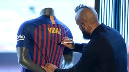 Pemain baru Barcelona, Arturo Vidal menandatangani jersey dalam presentasi resminya di Stadion Camp Nou, Barcelona, Spanyol, Senin (6/8). (Josep LAGO/AFP)