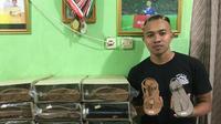 Pemain Persita Tangerang, Redi Rusmawan, bersama produksi sandal yang merupakan bisnis keluarganya. (Bola.com/Permana Kusumadijaya)