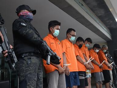 Petugas menghadirkan tersangka dalam rilis tindak pidana pemalsuan surat hasil tes PCR dan swab antigen di Polda Metro Jaya, Selasa (13/7/2021). Polda Metro Jaya menangkap dua tersangka berinsial NI dan NFA itu ditangkap di Tangerang, Banten pada Sabtu, 10 Juli 2021. (merdeka.com/Imam Buhori)