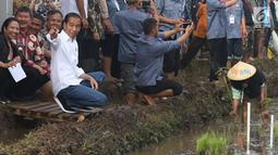 Presiden Joko Widodo didampingi Menteri BUMN Rini Soemarno saat blusukan ke area persawahan untuk meninjau Gerakan Mengawal Musim Tanam Okmar 2018/2019 di Desa Leuwigoong, Garut, Jawa Barat, Sabtu (19/1). (Liputan6.com/Angga Yuniar)