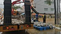 Dinas PUPR Kota Tangerang membuat tanggul sementara dengan barier beton dan karung berisi pasir. (Pramita/Liputan6.com).