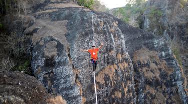 Gambar pada 9 September 2019 memperlihatkan atlet olahraga ekstrem, Andi Ardi berjalan di atas tali yang menggantung di ketinggian 740 meter (2.427 kaki) di Gunung Nglanggeran, Yogyakarta. Aksi itu sebagai bagian dari kampanye pariwisata untuk mempromosikan tempat yang indah. (AGUNG SUPRIYANTO/AFP)
