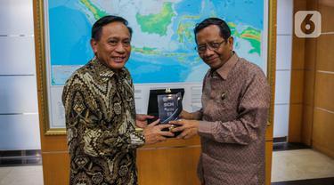 Direktur SCM Imam Sudjarwo (kiri) memberikan cenderamata kepada Menko Polhukam Mahfud Md di Kantor Kemenko Polhukam, Jakarta, Kamis (12/3/2020). Jajaran Grup Emtek mengunjungi Mahfud Md untuk bersilatuhrami. (Liputan6.com/Faizal Fanani)