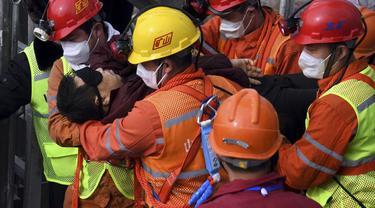 Tim penyelamat membawa seorang penambang yang terjebak di tambang ke ambulans di Kota Qixia di Provinsi Shandong, Tiongkok timur, Minggu, 24 Januari 2021.