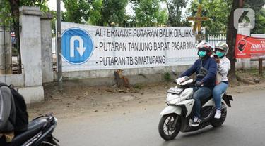 Pengendara motor melintasi spanduk pemberitahuan di merupakan jalur putar balik kawasan Lenteng Agung, Jakarta, Kamis (14/11/2019). Mulai 15 November 2019, jalur putar balik tersebut akan ditutup terkait pembangunan flyover yang saat ini telah mulai dikerjakan. (Liputan6.com/Immanuel Antonius)