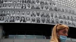 Potret para petugas kesehatan yang ditempelkan di bagian depan Bastille Opera di Paris, Prancis, Jumat (10/7/2020). Potret hitam putih untuk memberi penghormatan kepada pekerja medis Covid-19 itu merupakan kreasi seniman Prancis dan fotografer JR. (AP Photo/Francois Mori)