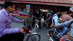 Sejumlah pengendara motor melewati kolong sebuah truk kontainer di Rawalpindi, Pakistan (28/10). Tanpa rasa takut para pengendara motor tersebut melintasi kolong truk yang membawa peti kemas. (Reuters/Faisal Mahmood)