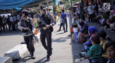 Pasukan Brimob Polda Metro Jaya bersenjata lengkap patroli di Terminal Kampung Rambutan, Jakarta, Selasa (19/6). Penjagaan dilakukan untuk memberi rasa aman kepada pemudik pada arus balik Lebaran 2018. (Liputan6.com/Faizal Fanani)