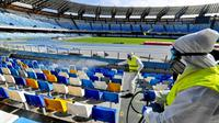 Petugas kesehatan melakukan pencegahan virus corona dengan melakukan sterilisasi di Stadion San Paolo. (AFP)