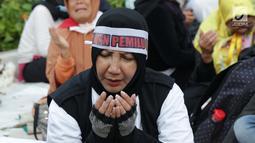 Peserta aksi massa Gerakan Nasional Kedaulatan Rakyat berdoa bersama saat unjuk rasa di depan Gedung Bawaslu, Jalan MH Thamrin, Jakarta, Selasa (21/5/2019). Dalam aksinya, mereka Bawaslu memeriksa hasil Pemilu 2019 yang dinilai banyak terdapat kecurangan. (Liputan6.com/Helmi Fithriansyah)